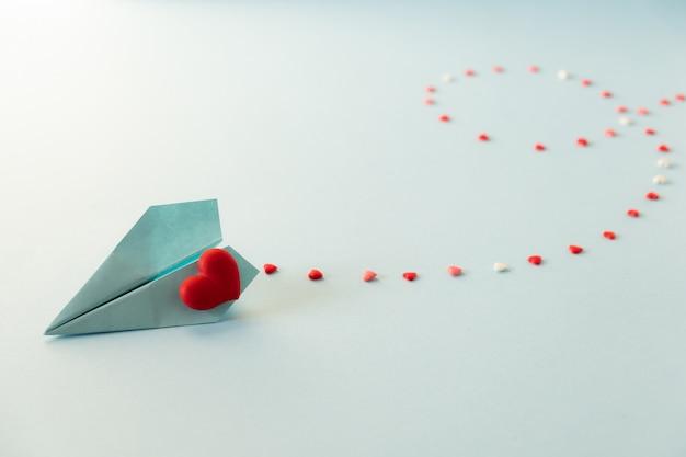 Enkele blauwe papieren vliegtuig met rode harten op een pastel blauwe tafel.