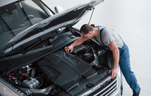 Enkele finishing moves. man in blauw uniform werkt met kapotte auto. reparaties maken.