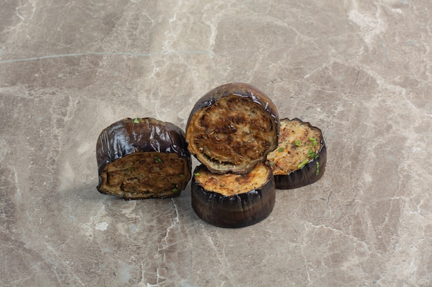 Enkele gebakken plakjes aubergine op marmeren tafel.