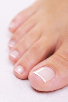 Enkele goed verzorgde vrouwelijke voet met een franse pedicure. closeup speelgoed.