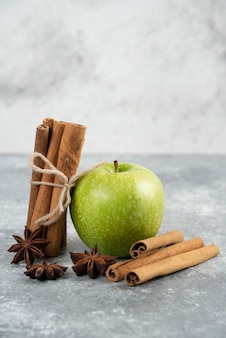 Enkele groene appel en kaneelstokjes op marmeren tafel.