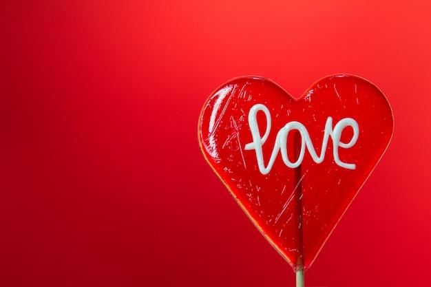 Enkele hartvormige lollipop met liefde teken op rode achtergrond