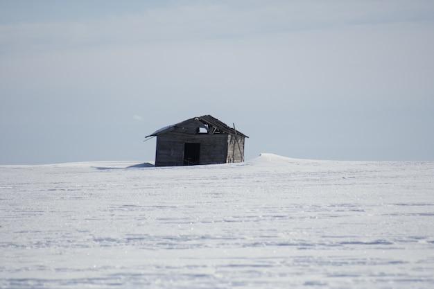 Enkele houten cottage in de winter overdag