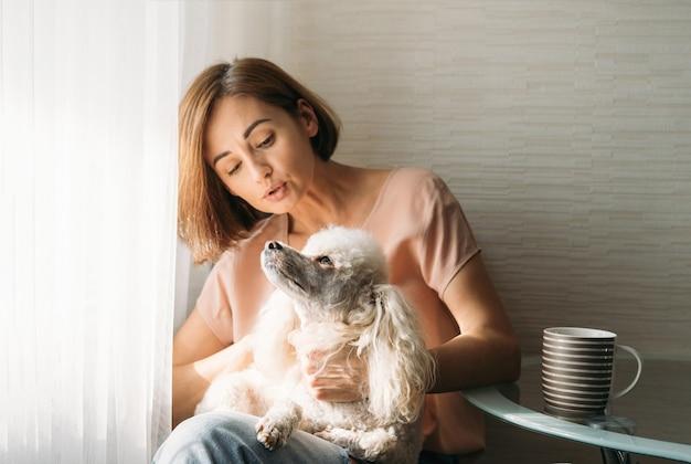 Enkele jonge brunette vrouw met poedel hond op handen bij het raam thuis zitten