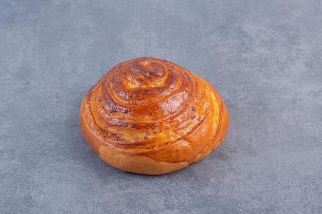 Enkele, knapperige zoete broodje weergegeven op marmeren achtergrond. hoge kwaliteit foto