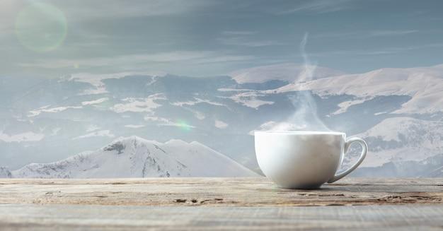 Enkele kopje thee of koffie en landschap van bergen op de achtergrond. kop warme drank met sneeuwachtige blik en wolkenlucht ervoor. warm in de winterdag, vakantie, reizen, nieuwjaar en kersttijd.