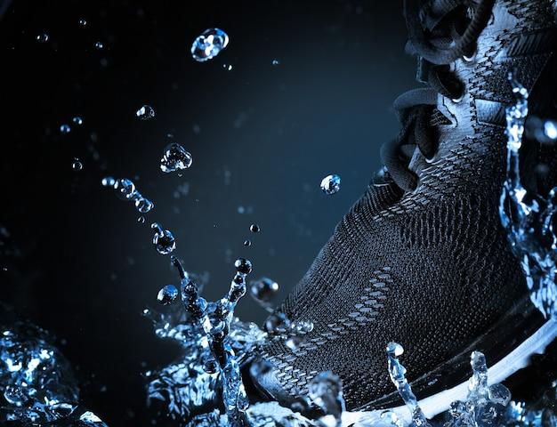 Enkele merkloze zwarte hardloopschoen of sneakers met waterspatten op zwarte achtergrond