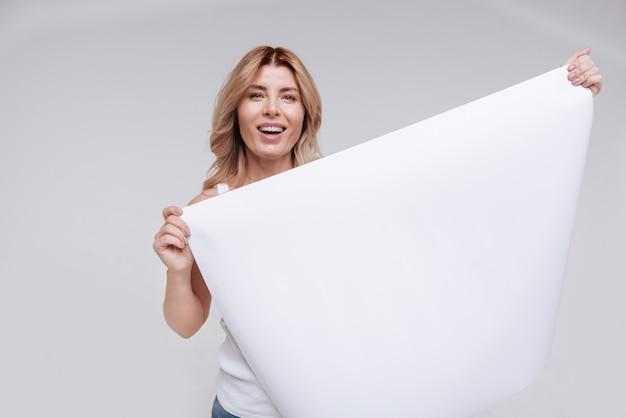Enkele nuttige informatie. bemoedigende stralende jonge vrouw die een groot leeg vel papier vasthoudt terwijl ze staat en glimlacht