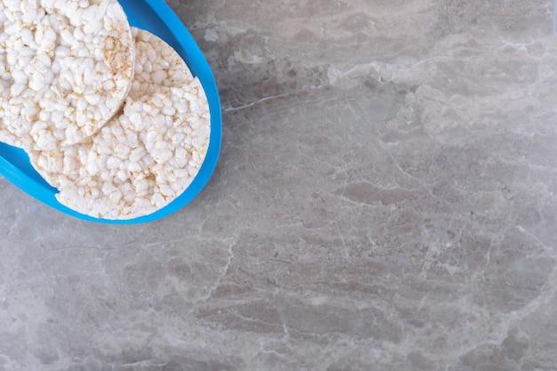 Enkele rijstwafels op het bord, op het marmeren oppervlak