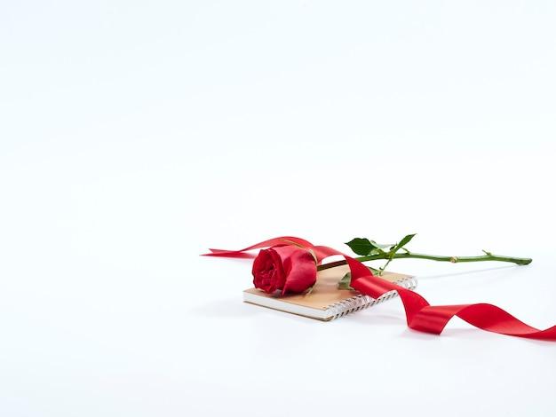 Enkele rode roos op een dagboek
