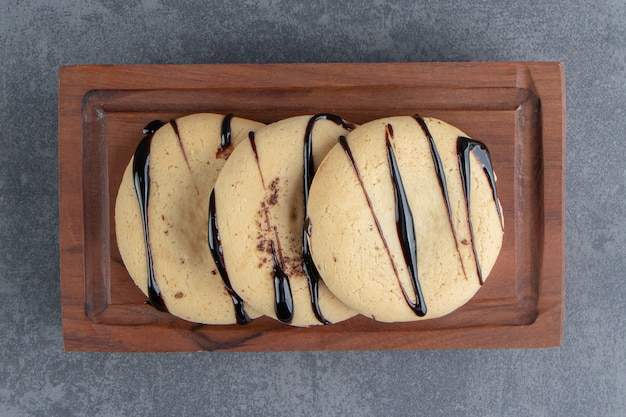 Enkele ronde koekjes met chocolade op een houten bord