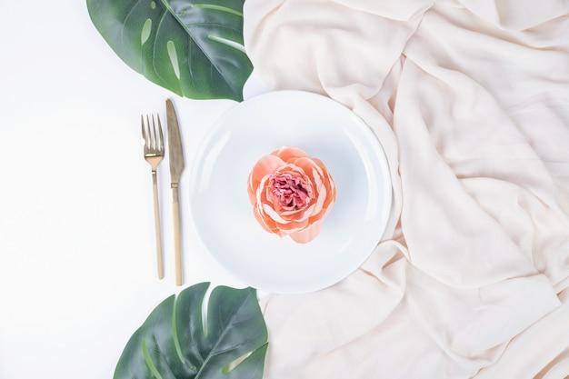 Enkele roos op een witte plaat met nep bladeren en tafelkleed.