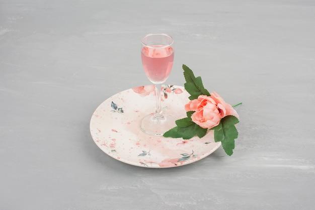 Enkele roze roos en een glas rose wijn op roze plaat