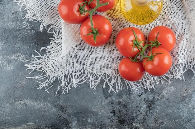 Enkele sappige tomaten met een glazen fles olie.