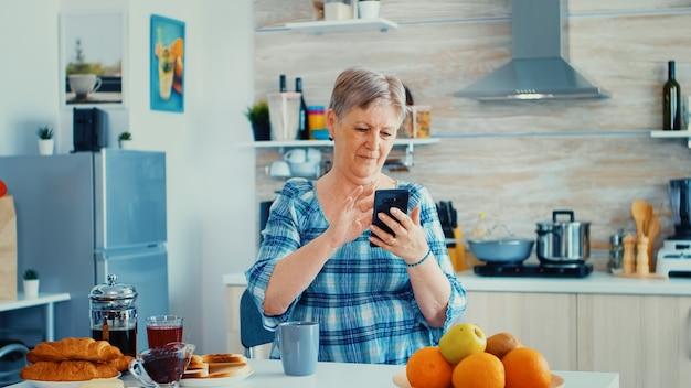 Enkele senior vrouw surfen op de telefoon in de keuken tijdens het ontbijt. authentieke bejaarde die moderne smartphone-internettechnologie gebruikt. online communicatie verbonden met de wereld, senioren vrije tijd