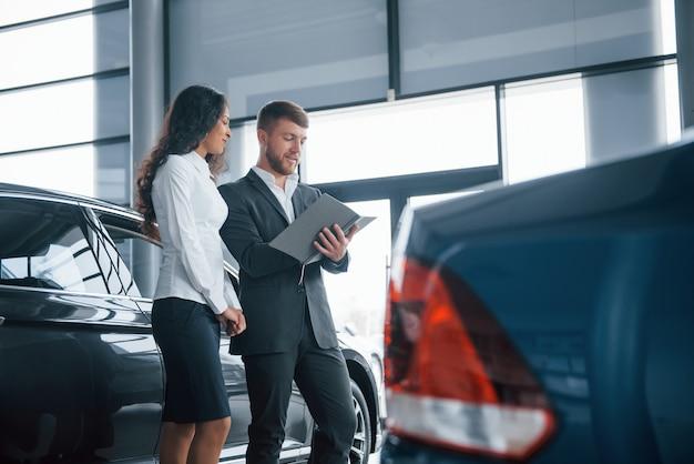 Enkele serieuze deals. vrouwelijke klant en moderne stijlvolle bebaarde zakenman in de auto-salon