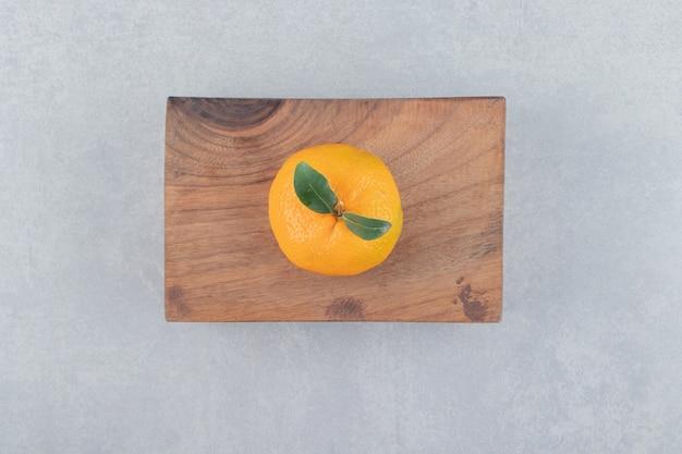 Enkele smakelijke clementine op een houten bord.