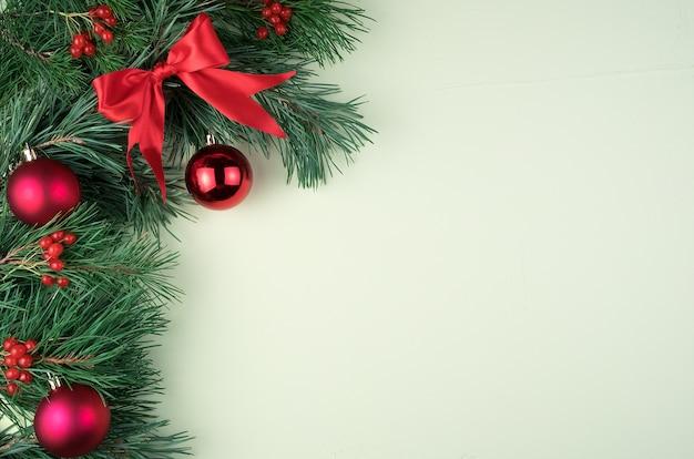 Enkele takken versierd met rood kerstspeelgoed, strikken en glazen bollen