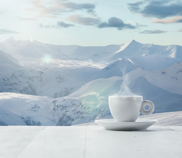 Enkele thee of koffie kopje en landschap van bergen op de achtergrond. kop warme drank met sneeuwachtige blik en wolkenlucht ervoor. warm in de winterdag, vakantie, reizen, nieuwjaar en kersttijd.