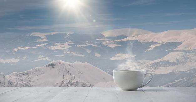 Enkele thee of koffiemok en landschap van bergen op de achtergrond. kop warme drank met sneeuwachtige blik en wolkenlucht ervoor. warm in de winterdag, vakantie, reizen, nieuwjaar en kersttijd.