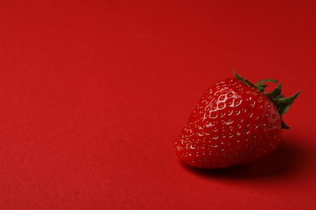 Enkele verse smakelijke aardbei op rood oppervlak