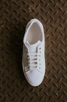 Enkele witte canvas sneakers op metalen vloer