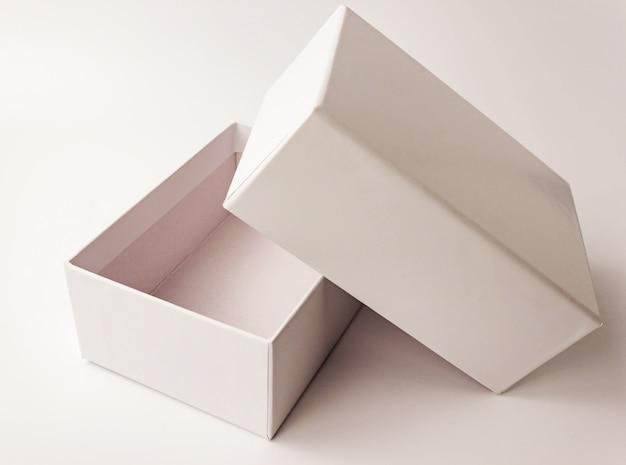 Enkele witte kleur papieren kartonnen doos op licht. close-up bekijken. selectieve zachte focus. tekst kopie ruimte. verpakking, transport, bewegend, huidig concept