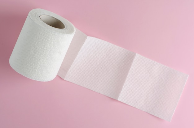 Enkele witte wc-papierrol op pastelroze