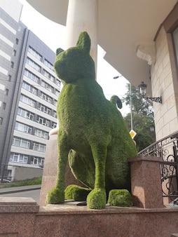 Enorm decoratief beeld van een kattenprofiel gemaakt van groen zacht materiaal in de buurt van de winkel