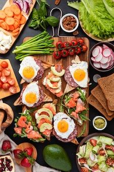 Enorm gezond ontbijt met broodjes met roerei, worst, zalm, rucola, kwark, avocado op een houten bord, zongedroogde tomaten