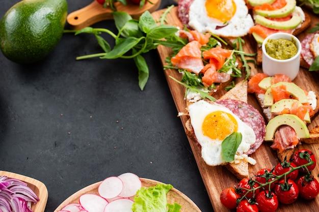 Enorm gezond ontbijt met broodjes met roerei, worst, zalm, rucola, kwark, avocado op een houten bord