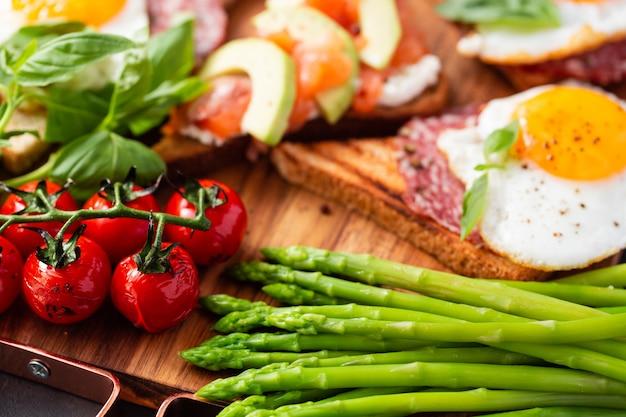 Enorm gezond ontbijt met broodjes met roerei, worst, zalm, rucola, kwark, avocado