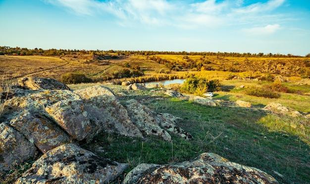 Enorme afzettingen van oude steenmineralen bedekt met vegetatie in een weiland vol warme zon in het pittoreske oekraïne en zijn prachtige natuur