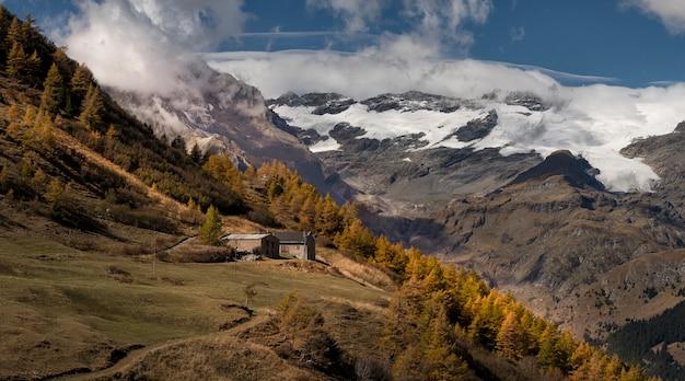 Enorme besneeuwde bergen in de herfst met kleurrijke bomen