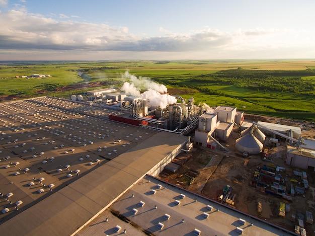 Enorme betoncentrale met pijpen tussen de velden. luchtfoto