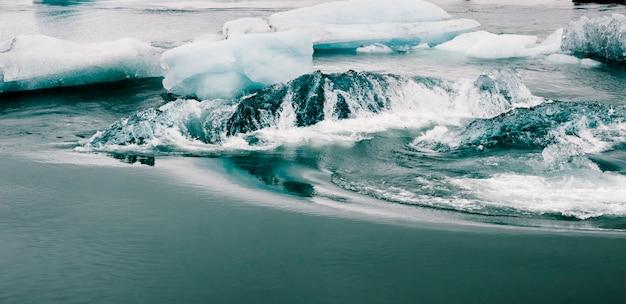 Enorme blokken ijs op ijskoude rivier en blauwe ijsbergen op jokulsarlon gletsjermeer.