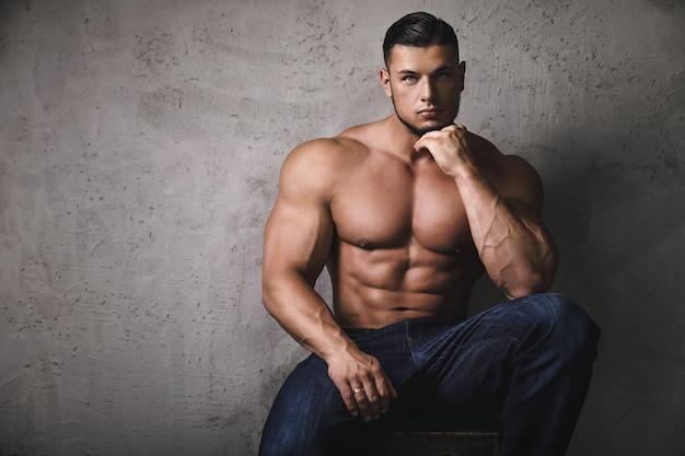 Enorme brute bodybuilder poseren naast de betonnen muur