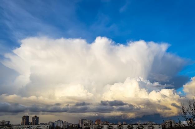Enorme cumulonimbuswolk boven de stad, 's avonds.