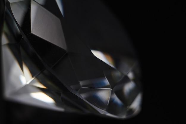 Enorme diamant en verschillende chique kristallen op een gradiënt spiegelend oppervlak, glinsteren en schitteren