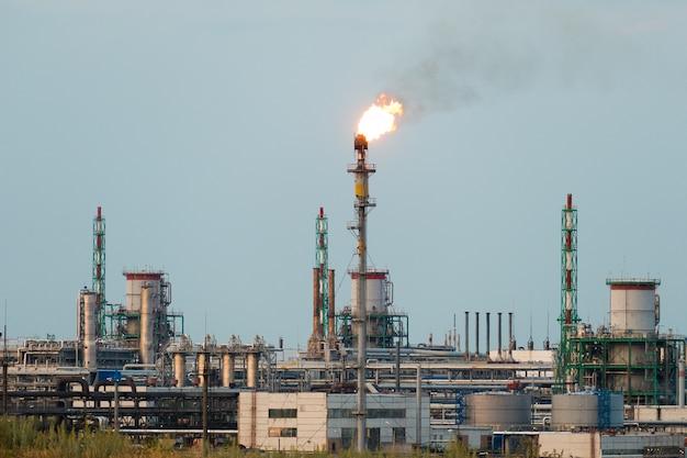Enorme gas- en olie verwerkingsfabriek met brandende fakkels, leidingen en destillatie van het complex.