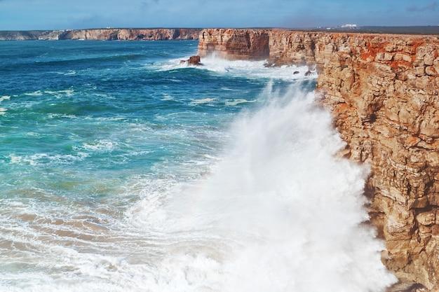 Enorme golven slaan tegen de rotsen.