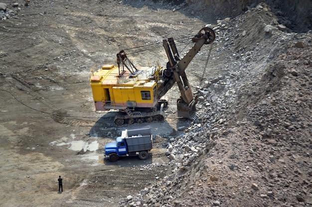 Enorme graafmachine en een vrachtwagen in een granietgroeve