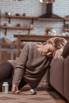 Enorme hoeveelheid. rijpe blonde vrouw die in slaap valt na het nemen van een enorme hoeveelheid medicatie