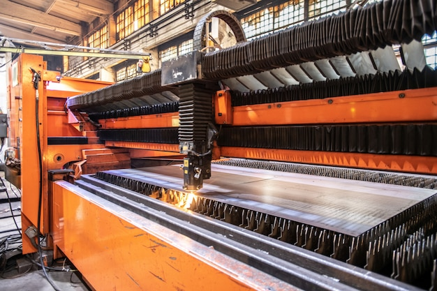 Enorme industriële machine die metalen werkstuk of plaat verwerkt met stroom van snijbalken in de fabriek