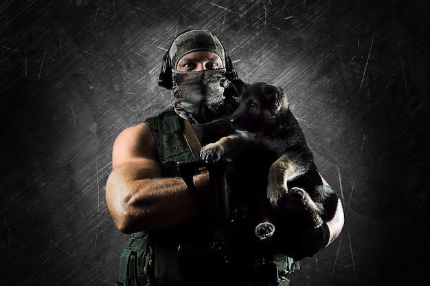 Enorme militaire man houdt een kleine puppy in zijn armen. gemengde media