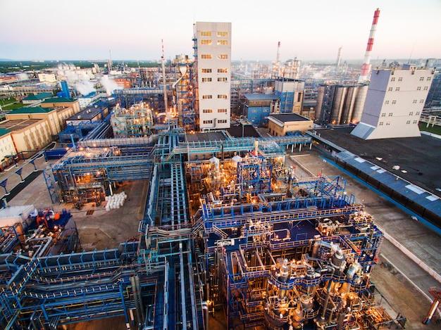 Enorme olieraffinaderij met metalen structuren, pijpen en destillatie van het complex met brandende lichten in de schemering. luchtfoto