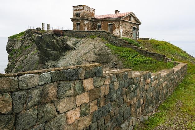 Enorme rotsen op de oceaan, zee zomer landschap, oud stenen gebouw en hek op een hoge klif, gamova vuurtoren, rusland, rusland, primorsky krai, peter de grote baai, babkin's kaap.