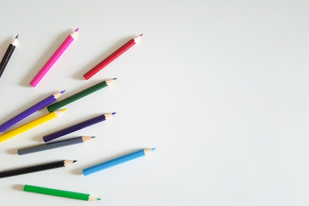 Enorme set van kleurrijke potloden op witte tafel achtergrond. bovenaanzicht.