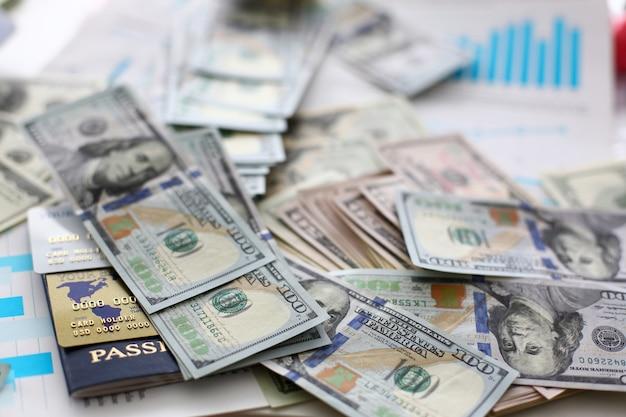 Enorme stapel van ons geldpaspoort en bankkaarten liggend op afbeeldingen van financiële statistieken