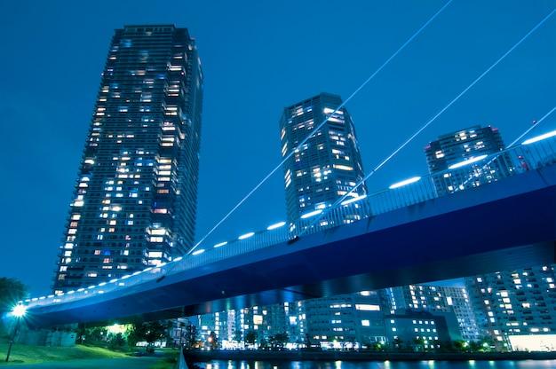 Enorme woonwolkenkrabbers met verlichte ramen voorbij de verlichte hangbrugstructuur in tokio, japan